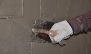 A plasterer rendering a wall.