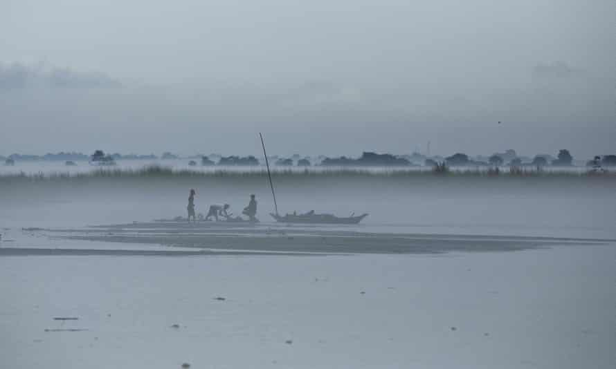 Indian villagers salvage logs of wood brought by floodwaters. The Brahmaputra river has burst its banks in many places and has been at danger levels for weeks.