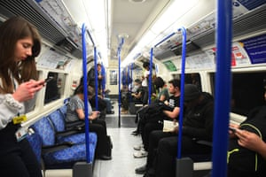 A few people social distancing on a tube train