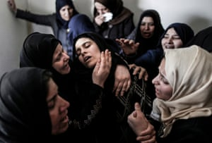 Mourners console the mother of 15-year-old Palestinian teenager Azzam Oweida during his funeral  in the southern Gaza Strip.