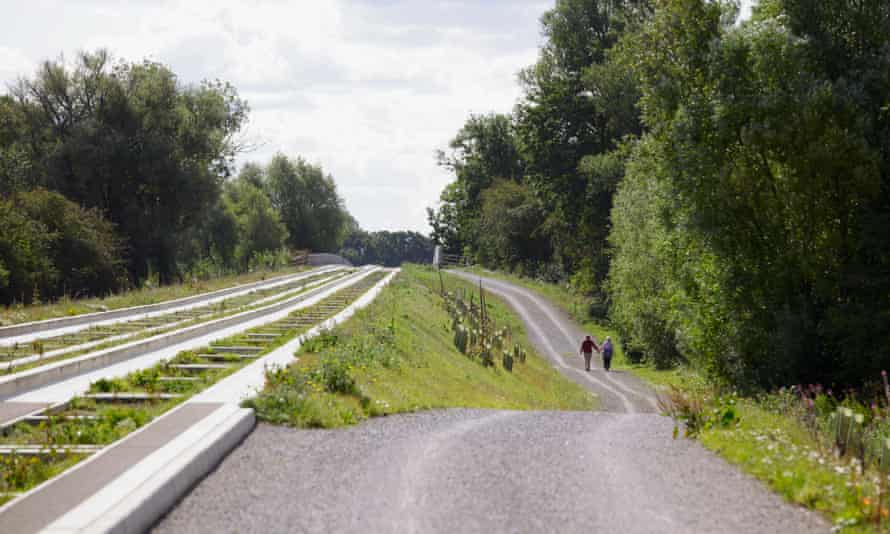 Couple walking beside Cambridge Guided Busway at St Ives.