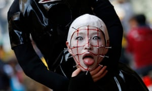 A participant in costume poses for a picture before a Halloween parade in Kawasaki, south of Tokyo, Japan. More than 100,000 spectators turned up to watch the parade, where 2,500 participants dressed up in costumes