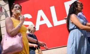 Shoppers on busy high street with sale sign in window