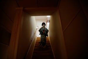 Tokijyo Hanasaki, a jiutamai dancer, wears a face mask as she walks down a flight of stairs at a studio