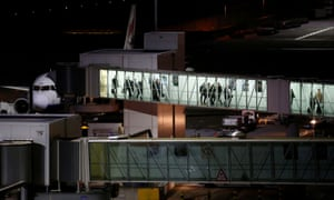 People disembark from an aircraft at Heathrow airport