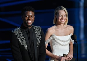 Chadwick Boseman steps up onstage to present the Best Adapted Screenplay award with Margot Robbie