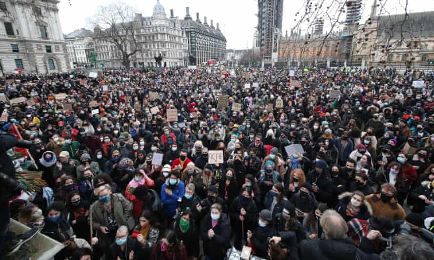 A large crowd of people holding placards gather in Parliament Square in London on Sunday, the day after clashes between police and crowds who gathered on Clapham Common on Saturday night to remember Sarah Everard.