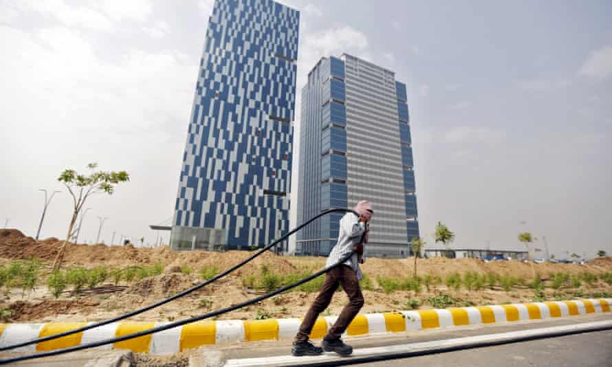 A labourer pulls cable in front of office buildings in Gujarat International Finance Tec-City at Gandhinagar.