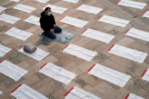 A man wearing a protective facemask prays next to predefined space intalled in order to follow the rules of social distancing ahead of the Eid Al-Fitr prayer, at The Grand Mosque of Durres, on May 24, 2020 on the first day of the Muslim festival marking the end of the holy fasting month of Ramadan.