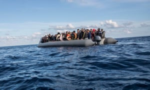 Migrants sit in a rubber dinghy