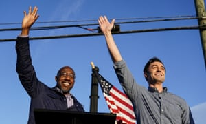 Rev. Raphael Warnock, left, and Jon Ossoff, right, gesture toward a crowd during a campaign rally in Marietta, Georgia.