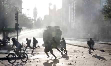 People and demonstrators run as a riot police vehicle uses a water cannon during a protest against Chile's government in Santiago, Chile.