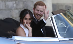 Harry and Meghan waving from open top car.