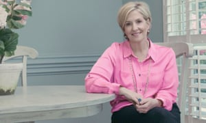 Brené Brown, smartly dressed and sitting sideways at a table, smiling at the camera