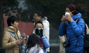 A man smokes beside a family putting on their masks