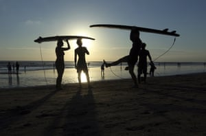 Bali, Indonesia Surfers carry their boards at sunset