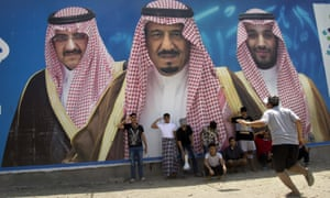 Saudi boys play in front of a billboard showing King Salman flanked by Mohammed bin Salman (right) and Mohammed bin Nayef.