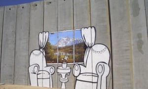 Banksy highlights the huge obstacle of the Israeli West Bank Barrier during a visit to Ramallah in Palestine.