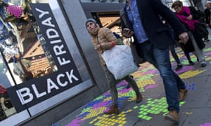 Shoppers pass a retail store's Black Friday promotion on Oxford Street in central London.