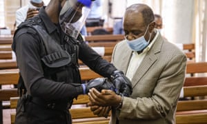 A police officer wearing gloves and a visor attaches handcuffs to the wrists of Paul Rusesabagina, who is wearing a beige suit and blue surgical mask