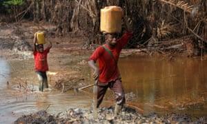 A man and his son walk through polluted farmland in Bayelsa, Nigeria