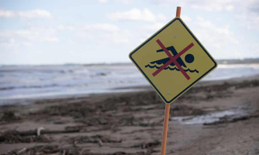 A no swimming warning at Old Bar Beach with high silt content from the recent floods, hay bales and dead livestock littering the beach east of Taree, Australia