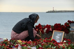 A woman lights a candle by a portrait of the well-known Russian charity worker Elizaveta Glinka at a memorial on the shores of the Black Sea
