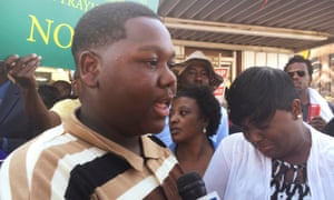 Cameron Sterling speaks as his mother looks on in front of a Louisiana convenience store where his father was killed by police in Baton Rouge on 13 July 2016.