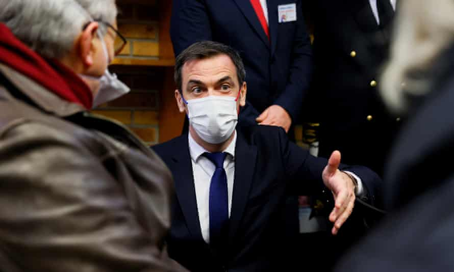 Olivier Véran, the French health minister, speaks to people waiting to receive a Covid vaccine