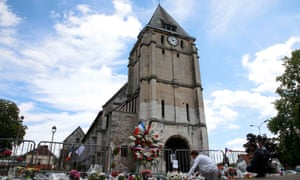 A woman places flowers near the church in Saint-Étienne-du-Rouvray, France, where Father Jacques Hamel was killed.