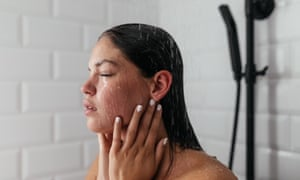 Young woman in bathroom taking a shower and washing her hair