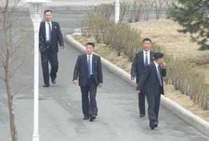 Men understood to be North Korean security guards patrol near the Far Eastern Federal University in Vladivostok
