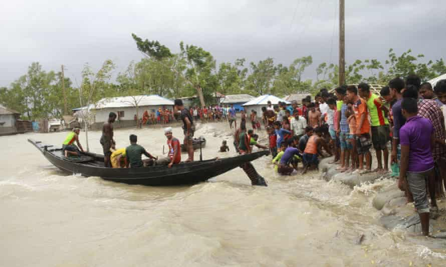 A boat brings people to land as flooding from Cylcone Amphan hit coastal areas in Bangladesh and India.