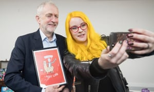 Jeremy Corbyn receives a gift that depicts him riding a llama, as he has a selfie taken with Katie Abey during a special event in Alfreton, Derbyshire on International Women's Day.
