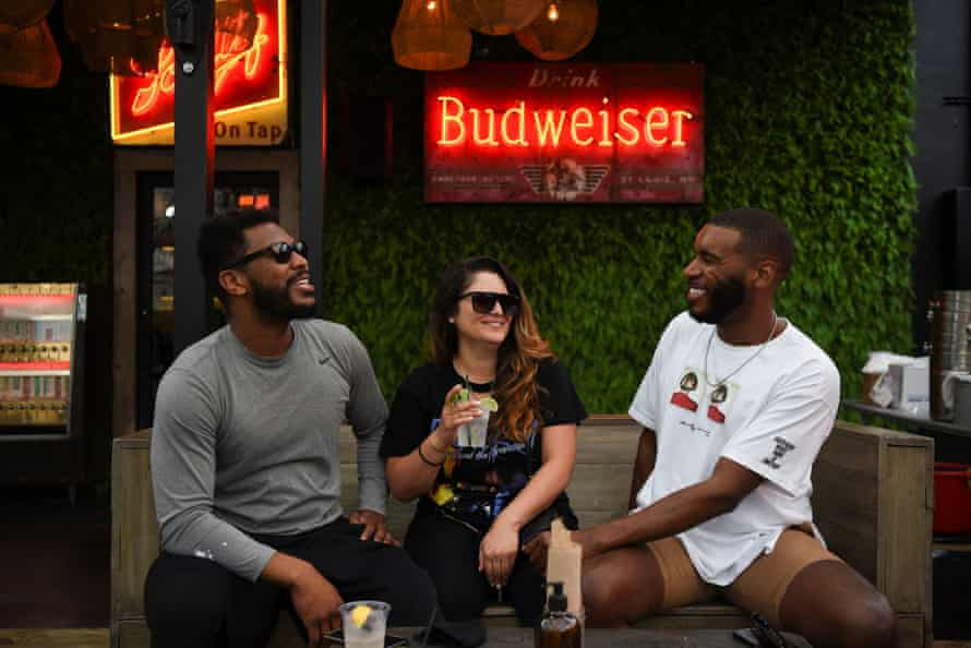 People share a drink on the patio at Bar 5015 as the state of Texas lifts its mask mandate.