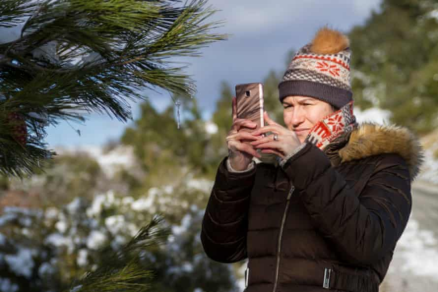 Woman taking a photo in winter (posed by model)