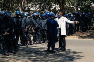Harare, Zimbabwe: A doctor speaks to riot police officers asking for safe passage during a protest by hundreds of Zimbabwean medical staff