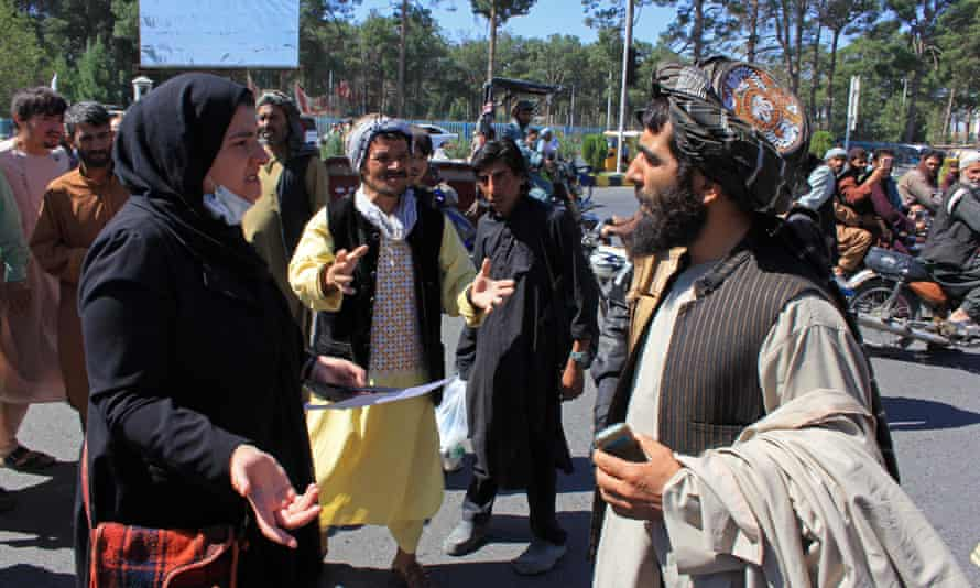 An Afghan woman speaks with a member of the Taliban during a protest in Herat