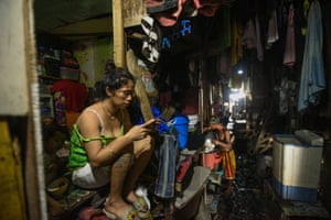 A woman checks her phone outside her home in Manila as the Philippines orders half its population to stay home