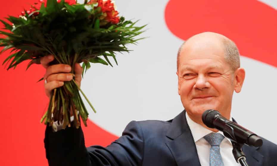 Olaf Scholz waves a bouquet of flowers after the election result