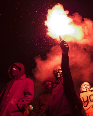 Masked protesters hold a flare as they stand on Nelson's Column