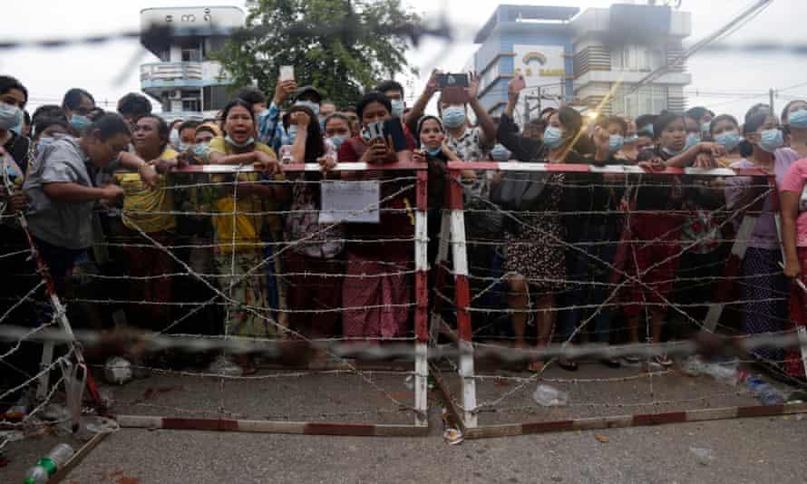 Orangorang menunggu di belakang barikade di luar penjara Insein, Yangon, 30 Juni, untuk pembebasan tahanan