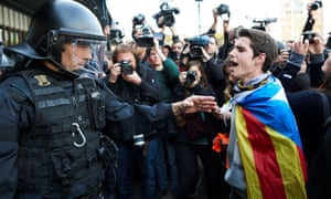 A man wrapped in the Catalan flag faces a riot police officer during a protest in Barcelona over the arrest of Carles Puigdemont.