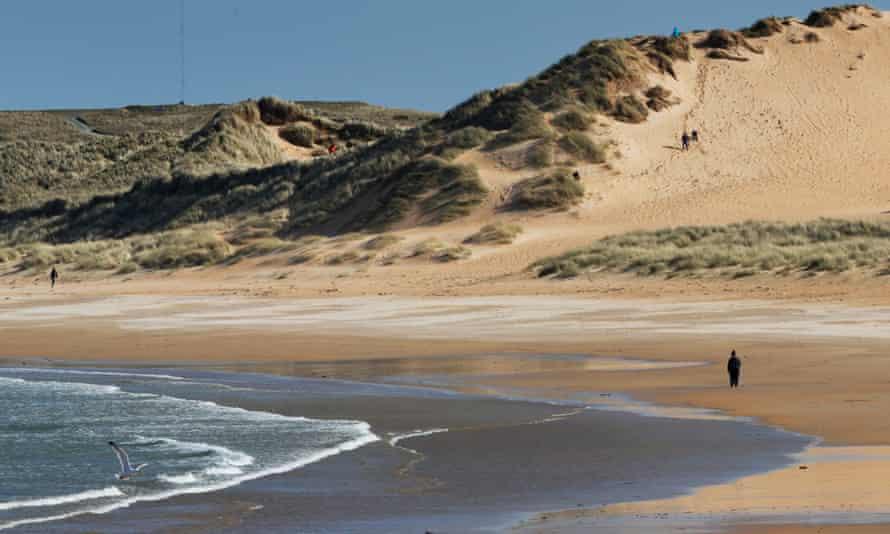 People take their daily exercise on Fraserburgh beach, Scotland, on 15 April