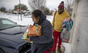 Nena and Howard Mamou take what they can from their home in the Glenwood neighborhood in Hutto, Texas, as they seek a hotel amid power outages.