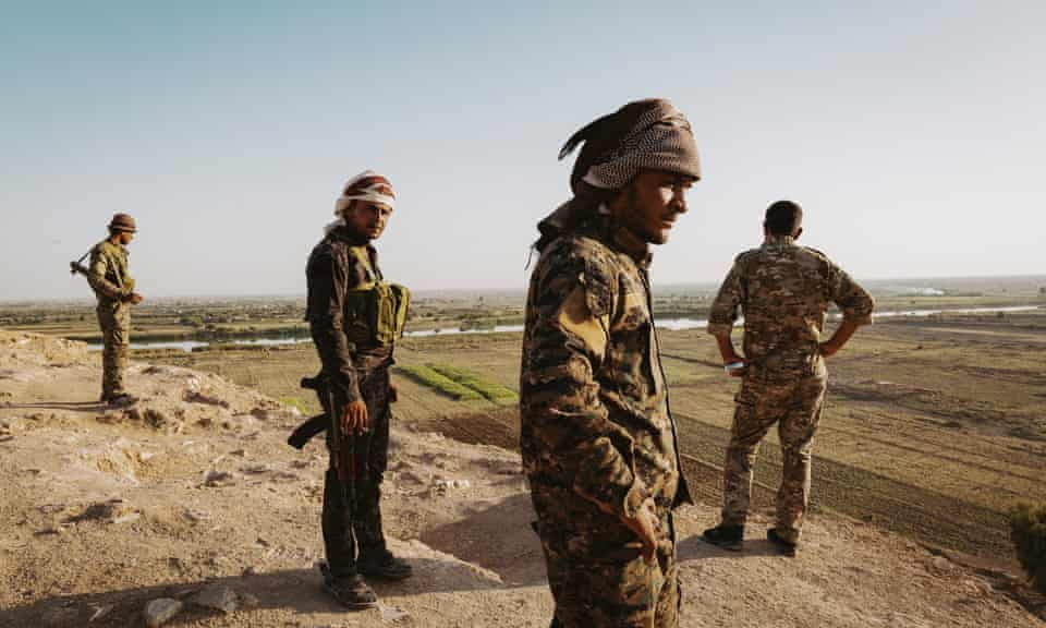 Soldiers of the Syrian Democratic Forces stand on a hill overlooking the Euphrates river, near the border with Iraq, in Deir ez-Zor province.