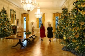 Staff members walk through the decorated East Room