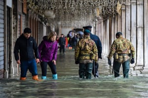 Visitors and security walk across a flooded arcade during an acqua alta, a meteorological phenomenon of high flood waters.