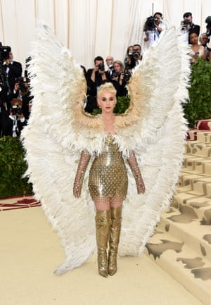 Heavenly = angel wings, right? Katy Perry arrived wearing a giant pair of feathered wings with her gold chainmail Versace mini dress and thigh-high boots. The singer and American Idol judge paused for a moment on the red carpet to kneel in prayer - perhaps hoping for divine guidance on how to sit down with those wings.