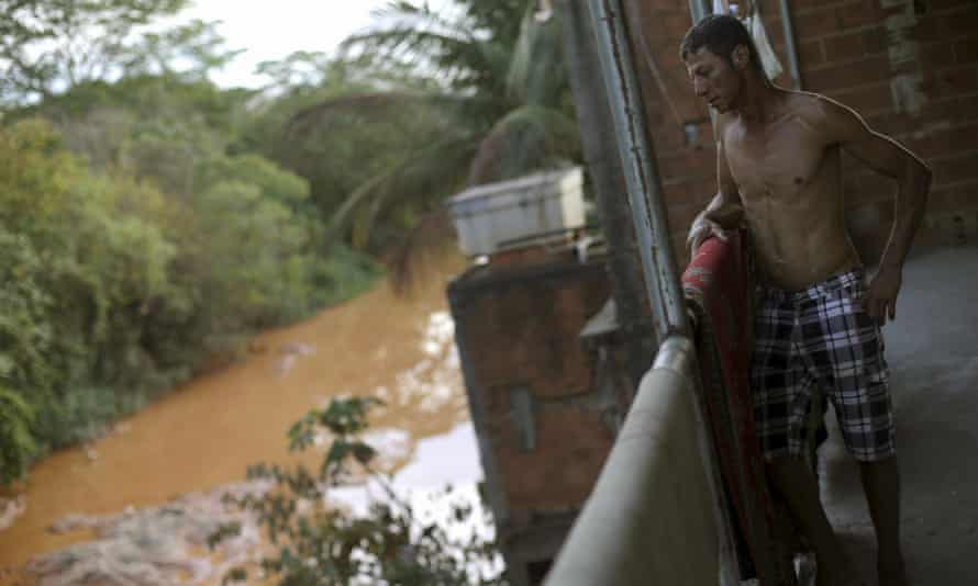 A resident is pictured on the balcony of his house on the banks of Rio Doce after a dam, owned by Vale and BHP Billiton, burst.